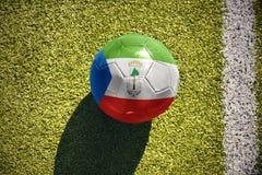 Fußballball mit der Staatsflagge der Äquatorialguinea liegt auf dem Feld Lizenzfreie Stockbilder