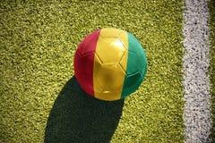 Fußballball mit der Staatsflagge der Guine liegt auf dem Feld stockbilder