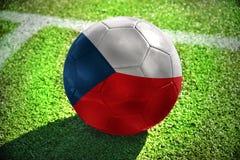 Fußballball mit der Staatsflagge der Tschechischen Republik liegt auf dem grünen Feld Stockfotografie