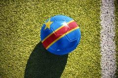 Fußballball mit der Staatsflagge des Demokratischen Republiken Kongo liegt auf dem Feld Stockfotografie