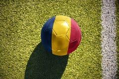 Fußballball mit der Staatsflagge des Konfettis liegt auf dem Feld Lizenzfreies Stockfoto