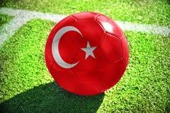 Fußballball mit der Staatsflagge des Truthahns liegt auf dem grünen Feld Stockfotografie