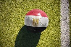 Fußballball mit der Staatsflagge von Ägypten liegt auf dem Feld Lizenzfreie Stockfotos