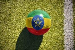 Fußballball mit der Staatsflagge von Äthiopien liegt auf dem Feld Lizenzfreies Stockbild