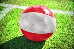Fußballball mit der Staatsflagge von Österreich liegt auf dem grünen Feld Lizenzfreie Stockfotografie