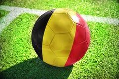 Fußballball mit der Staatsflagge von Belgien liegt auf dem grünen Feld Stockbilder
