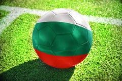 Fußballball mit der Staatsflagge von Bulgarien liegt auf dem grünen Feld Lizenzfreie Stockfotos