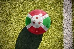 Fußballball mit der Staatsflagge von Burundi liegt auf dem Feld Lizenzfreies Stockbild