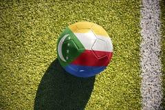 Fußballball mit der Staatsflagge von Comoren liegt auf dem Feld Stockfoto