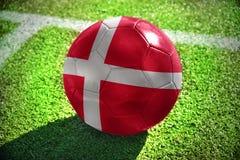 Fußballball mit der Staatsflagge von Dänemark liegt auf dem grünen Feld Lizenzfreie Stockbilder