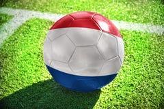 Fußballball mit der Staatsflagge von den Niederlanden liegt auf dem grünen Feld Lizenzfreie Stockfotos
