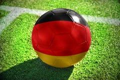 Fußballball mit der Staatsflagge von Deutschland liegt auf dem grünen Feld Lizenzfreie Stockfotografie