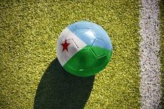Fußballball mit der Staatsflagge von Dschibouti liegt auf dem Feld Stockbild