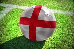 Fußballball mit der Staatsflagge von England liegt auf dem grünen Feld Lizenzfreie Stockfotos