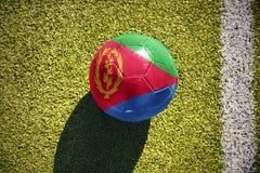 Fußballball mit der Staatsflagge von Eritrea liegt auf dem Feld Lizenzfreie Stockfotos