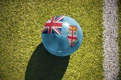 Fußballball mit der Staatsflagge von Fidschi liegt auf dem Feld Lizenzfreies Stockfoto