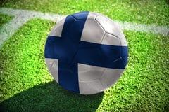 Fußballball mit der Staatsflagge von Finnland liegt auf dem grünen Feld Lizenzfreies Stockfoto