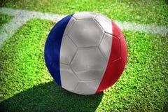Fußballball mit der Staatsflagge von Frankreich liegt auf dem grünen Feld Stockbild
