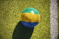 Fußballball mit der Staatsflagge von Gabun liegt auf dem Feld Lizenzfreies Stockfoto