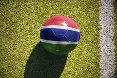 Fußballball mit der Staatsflagge von Gambia liegt auf dem Feld Stockfotos