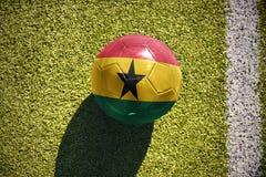 Fußballball mit der Staatsflagge von Ghana liegt auf dem Feld Stockfotografie