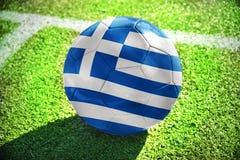 Fußballball mit der Staatsflagge von Griechenland liegt auf dem grünen Feld Lizenzfreie Stockfotografie