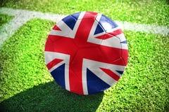 Fußballball mit der Staatsflagge von Großbritannien liegt auf dem grünen Feld Lizenzfreie Stockbilder