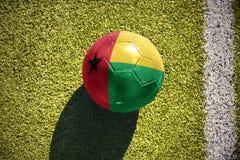 Fußballball mit der Staatsflagge von Guinea-Bissau liegt auf dem Feld Lizenzfreies Stockbild