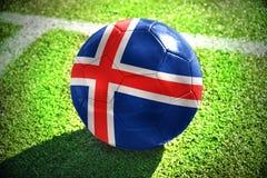 Fußballball mit der Staatsflagge von Island liegt auf dem grünen Feld Stockbilder