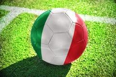 Fußballball mit der Staatsflagge von Italien liegt auf dem grünen Feld Stockbild