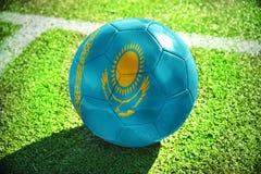 Fußballball mit der Staatsflagge von Kasachstan liegt auf dem grünen Feld Stockfoto