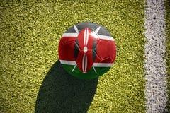Fußballball mit der Staatsflagge von Kenia liegt auf dem Feld Lizenzfreie Stockfotografie