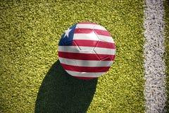 Fußballball mit der Staatsflagge von Liberia liegt auf dem Feld Lizenzfreies Stockbild