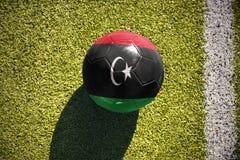 Fußballball mit der Staatsflagge von Libyen liegt auf dem Feld Lizenzfreie Stockfotos