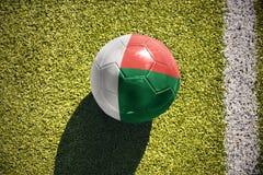 Fußballball mit der Staatsflagge von Madagaskar liegt auf dem Feld Stockfotos