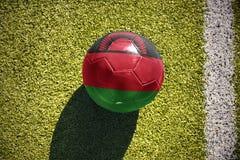 Fußballball mit der Staatsflagge von Malawi liegt auf dem Feld Stockbilder
