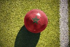 Fußballball mit der Staatsflagge von Marokko liegt auf dem Feld Lizenzfreies Stockfoto