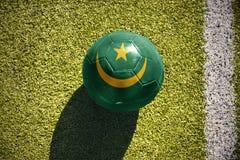 Fußballball mit der Staatsflagge von Mauretanien liegt auf dem Feld Stockbild