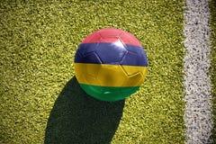 Fußballball mit der Staatsflagge von Mauritius liegt auf dem Feld Lizenzfreie Stockfotos