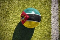 Fußballball mit der Staatsflagge von Mosambik liegt auf dem Feld Stockbilder