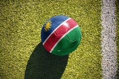 Fußballball mit der Staatsflagge von Namibia liegt auf dem Feld Lizenzfreie Stockfotografie
