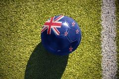 Fußballball mit der Staatsflagge von Neuseeland liegt auf dem Feld Lizenzfreies Stockbild