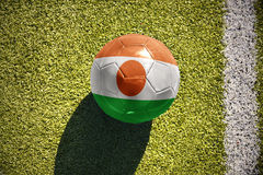 Fußballball mit der Staatsflagge von Niger liegt auf dem Feld Stockfoto