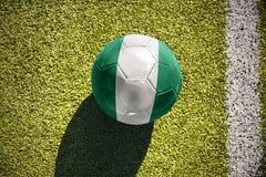Fußballball mit der Staatsflagge von Nigeria liegt auf dem Feld Lizenzfreies Stockbild