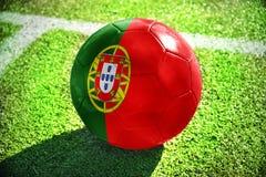 Fußballball mit der Staatsflagge von Portugal liegt auf dem grünen Feld Lizenzfreies Stockbild
