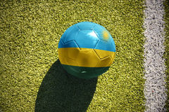 Fußballball mit der Staatsflagge von Ruanda liegt auf dem Feld Lizenzfreie Stockfotos