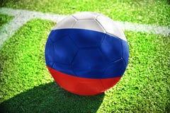 Fußballball mit der Staatsflagge von Russland liegt auf dem grünen Feld Stockbilder