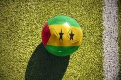 Fußballball mit der Staatsflagge von Sao Tome und Principe liegt auf dem Feld Stockfotografie