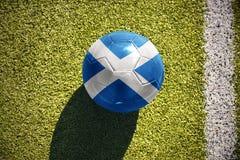 Fußballball mit der Staatsflagge von Schottland liegt auf dem Feld Lizenzfreie Stockfotos