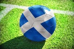Fußballball mit der Staatsflagge von Schottland liegt auf dem grünen Feld Lizenzfreies Stockbild